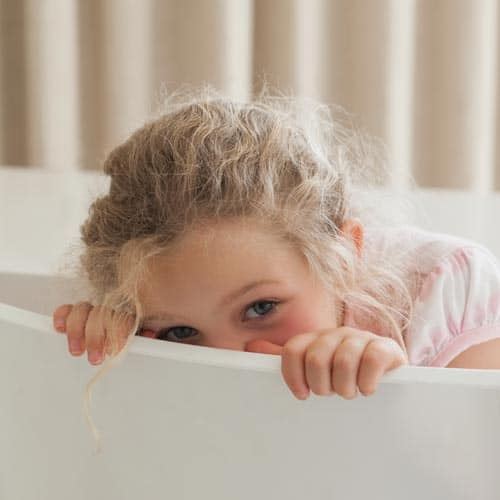 girl looking over the side of a bath